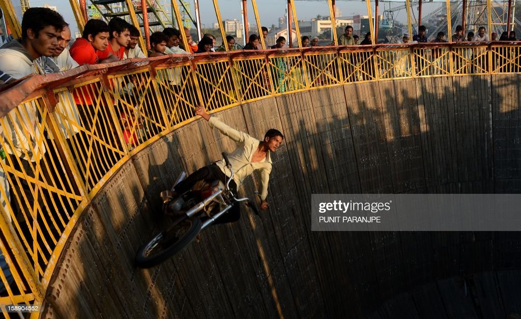 An Indian daredevil performs motorcycle stunts during an annual fair in Mumbai on January 3, 2013. The ten day-long fair is being held in honour of the Sufi saint Makhdoom Ali Mahimi on the dusty Mahim beach, which is full of people on giant wheels, toy trains and enjoying gravity-defying stunts in the 'Maut Ka Kuan' or 'Valley of Death'.