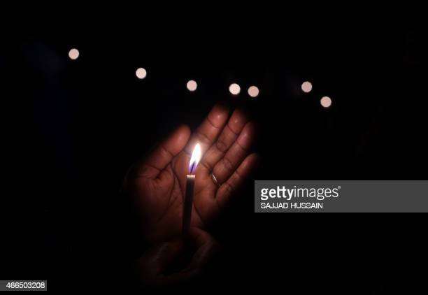 An Indian demonstrator holds a candle as she takes part in a vigil and silent protest against the alleged gangrape of a nun in the eastern state of...