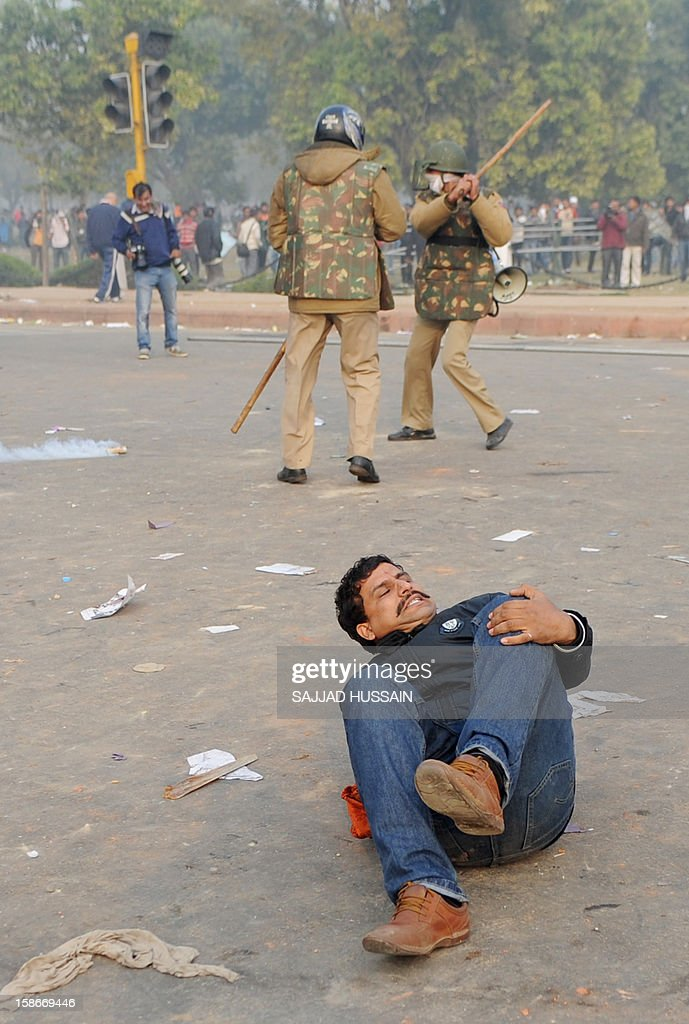 An Indian demonstrator lies injured on the ground after a police charge during a protest calling for better safety for women following the rape of a student last week, in front the India Gate monument in New Delhi on December 23, 2012. In the biggest protest so far, several thousand college students rallied at the India Gate monument in the heart of the capital where they were baton-charged, water cannoned and tear gassed by the police. AFP PHOTO/ Sajjad Hussain