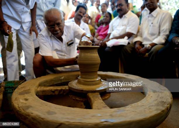 An Indian demonstrator makes an earthern pot during a protest demanding the free excavation of clay on governmentowned land in Chennai on May 8 2017...