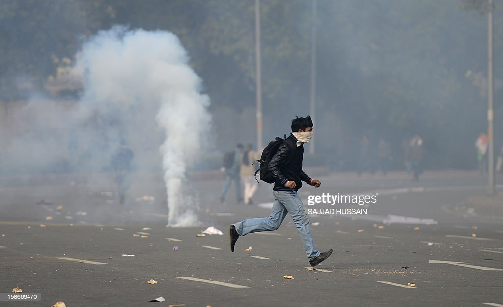 An Indian demonstrator runs past a tear gas canister during a protest calling for better safety for women following the rape of a student last week, in front the India Gate monument in New Delhi on December 23, 2012. In the biggest protest so far, several thousand college students rallied at the India Gate monument in the heart of the capital where they were baton-charged, water cannoned and tear gassed by the police. AFP PHOTO/ Sajjad Hussain