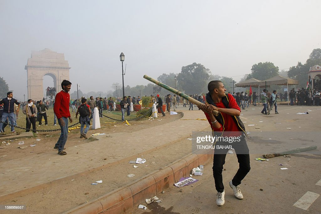 An Indian demonstrator throws a pole at police during a protest calling for better safety for women following the rape of a student last week, in front the India Gate monument in New Delhi on December 23, 2012. In the biggest protest so far, several thousand college students rallied at the India Gate monument in the heart of the capital where they were baton-charged, water cannoned and tear gassed by the police. AFP PHOTO/ TENGKU BAHAR