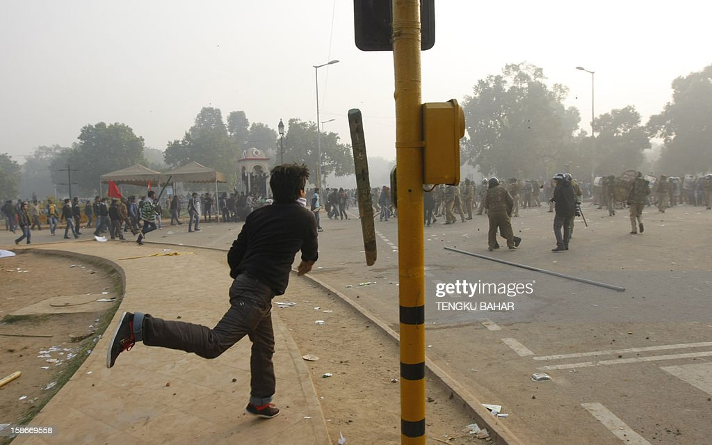 An Indian demonstrator throws a pole at police during a protest calling for better safety for women following the rape of a student last week, in front the India Gate monument in New Delhi on December 23, 2012. In the biggest protest so far, several thousand college students rallied at the India Gate monument in the heart of the capital where they were baton-charged, water cannoned and tear gassed by the police.