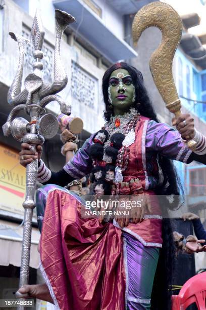 An Indian devotee dressed as goddess Kali Mata participates in a procession in Amritsar on November 12 on the occasion of the birth anniversary of...