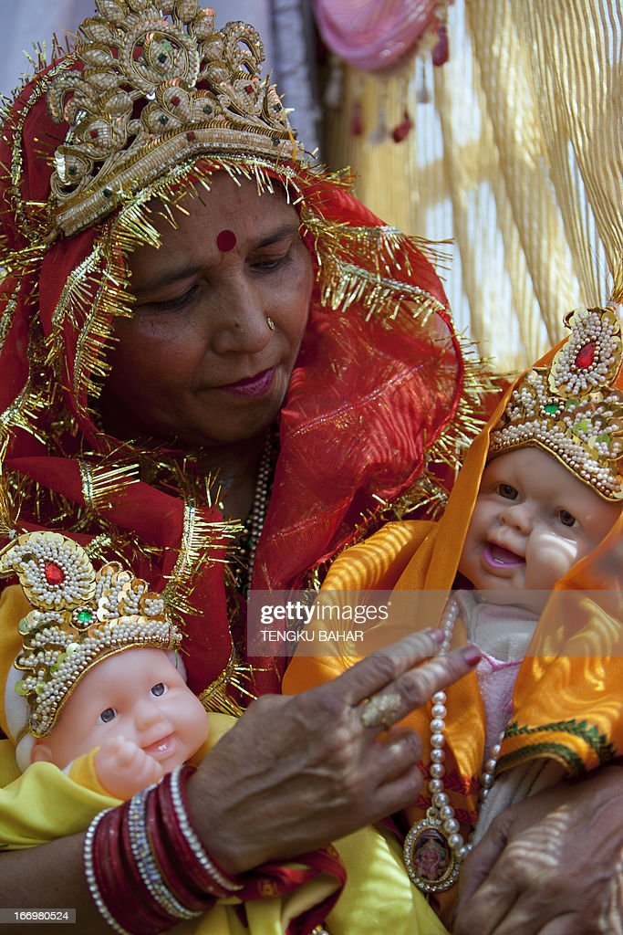 An Indian devotee, dressed as one of the three wives of King Deshrath, the father of Hindu god Lord Rama, sits with baby dolls one of which represents Lord Rama, as she waits to take part in a procession for Ram Navami, which marks the birthday of Hindu god Lord Rama, in New Delhi on April 19, 2013. Hindu devotees across the country are celebrating the festival of Ram Navami, the birth anniversary of Hindu Lord Rama, which also marks the end of the nine-day long fast of Navaratri. AFP PHOTO/TENGKU BAHAR