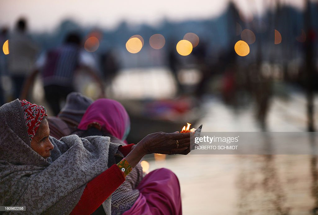 An Indian devotee holds up an offering alongside the waters of Sangam or confluence of the Yamuna, Ganges and mythical Sarawati rivers at sunset during the Maha Kumbh festival in Allahabad on February 8, 2013. The Kumbh Mela in the town of Allahabad will see up to 100 million worshippers gather over 55 days to take a ritual bath in the holy waters, believed to cleanse sins and bestow blessings.