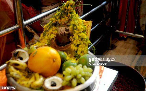 An Indian devotee is reflected in a mirror as she gathers with others at a temple in Chennai on April 14 on the occasion of Vishu or the New Year in...