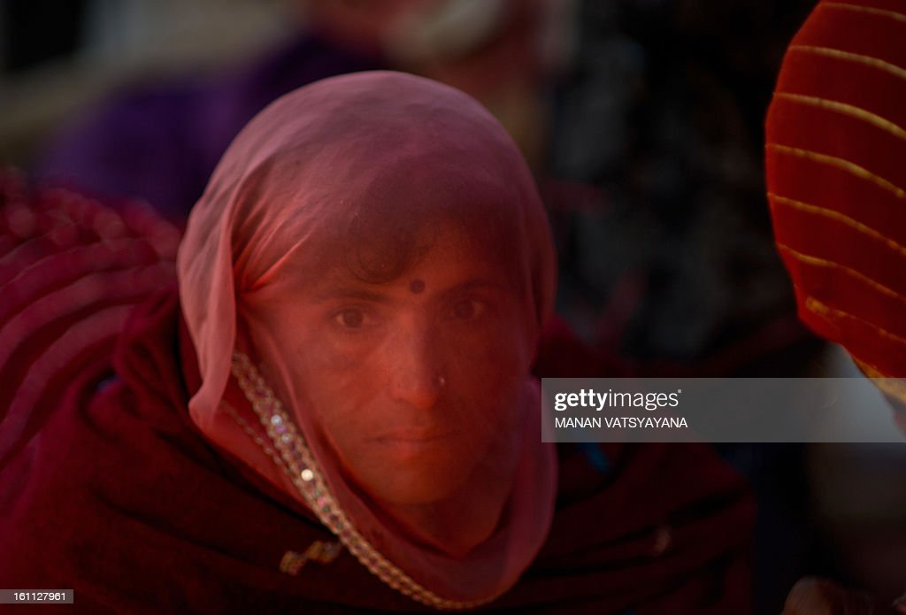 An Indian devotee looks through her veil as she offers prayers at the banks of Sangam or confluence of the Yamuna, Ganges and mythical Saraswati rivers during the Maha Kumbh festival in Allahabad on February 9, 2013. The Kumbh Mela in the town of Allahabad will see up to 100 million worshippers gather over 55 days to take a ritual bath in the holy waters, believed to cleanse sins and bestow blessings.