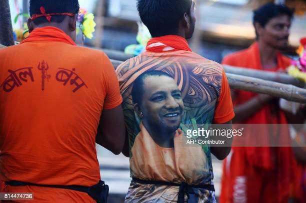 An Indian devotee of Lord Shiva wearing a Tshirt with a photo of Chief Minister of Uttar Pradesh Yogi Adityanath stands on the bank of river Ganga to...