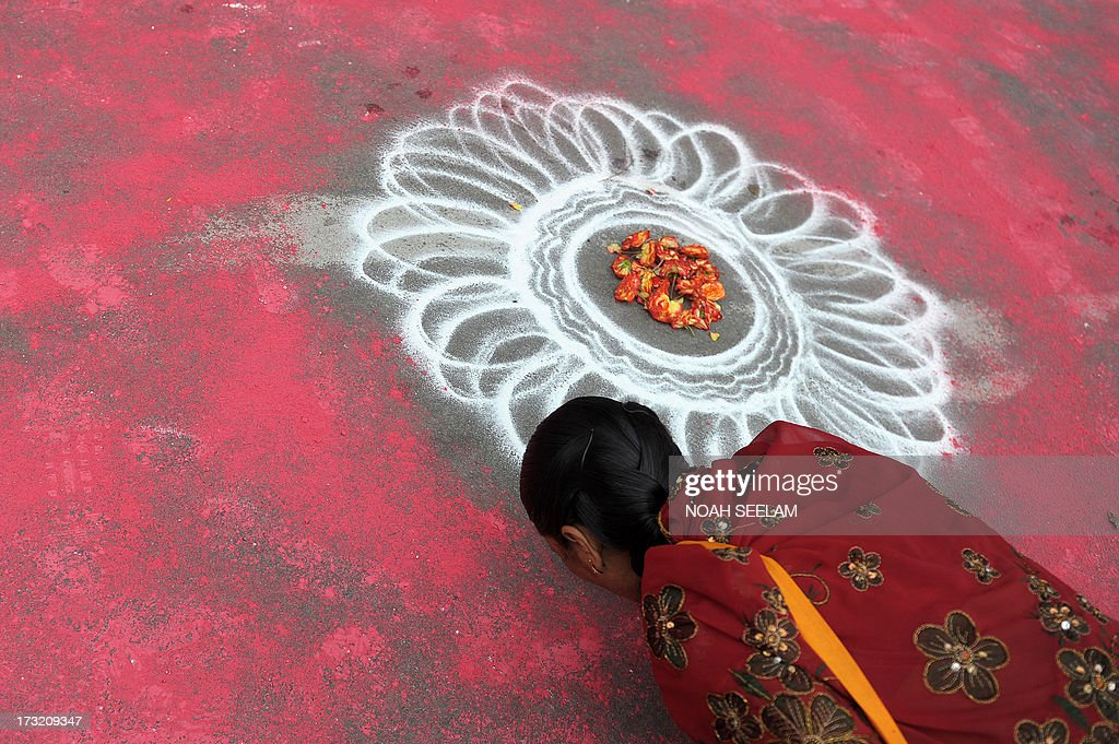 An Indian devotee of The International Society of Krishna Conciousness (ISKON) touches the ground at the start of the Sri Jagannatha Ratha Yatra in Hyderabad on July 10, 2013. According to mythology, the Ratha Yatra dates back some 5,000 years when Hindu god Krishna, along with his older brother Balaram and sister Subhadra, were pulled on a chariot from Kurukshetra to Vrindavana by Krishna's devotees. AFP PHOTO / Noah SEELAM