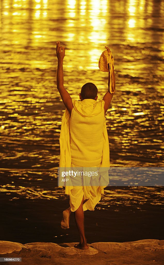 An Indian devotee performs evening prayers after taking a 'holy dip' in the waters of Sangam or confluence of the Yamuna, Ganges and mythical Sarawati rivers at sunset during the Maha Kumbh festival in Allahabad on February 8, 2013. The Kumbh Mela in the town of Allahabad will see up to 100 million worshippers gather over 55 days to take a ritual bath in the holy waters, believed to cleanse sins and bestow blessings. AFP PHOTO/SANJAY KANOJIA