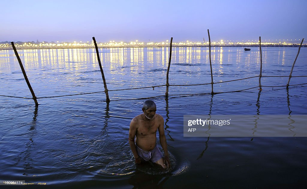 An Indian devotee returns after taking a 'holy dip' in the waters of Sangam or confluence of the Yamuna, Ganges and mythical Sarawati rivers at sunset during the Maha Kumbh festival in Allahabad on February 8, 2013. The Kumbh Mela in the town of Allahabad will see up to 100 million worshippers gather over 55 days to take a ritual bath in the holy waters, believed to cleanse sins and bestow blessings.