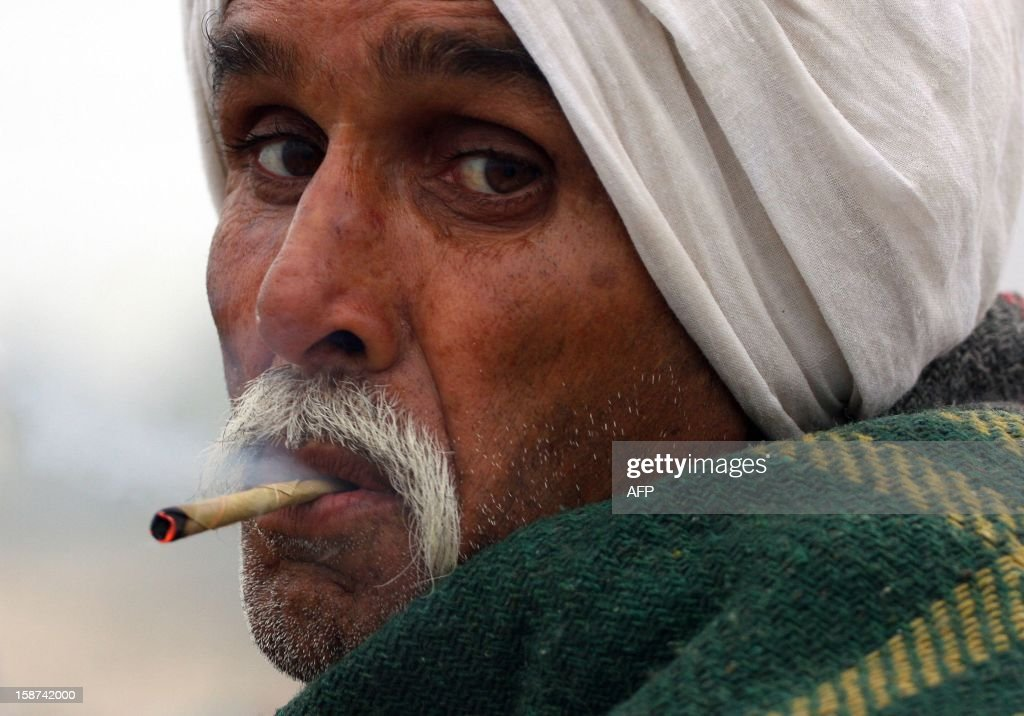 An Indian devotee smokes a 'Bidi' or local cigarette after taking a holy dip at 'Sangam' in Allahabad on December 27, 2012. 'Sangam' is the confluence of the Yamuna, Ganges and mythical Saraswati rivers in the northern Indian city, where The Maha Kumbh Mela is scheduled to take place in early 2013. AFP PHOTO/Sanjay KANOJIA
