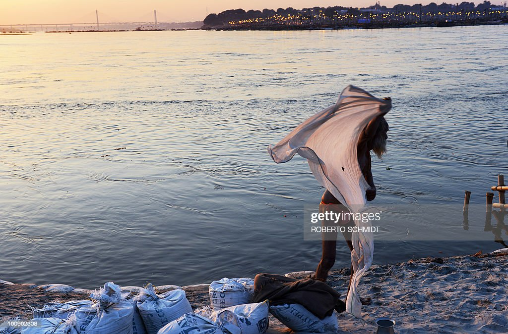 An Indian devotee wraps himself in a dhoti after taking a 'holy dip' in the waters of Sangam or confluence of the Yamuna, Ganges and mythical Sarawati rivers at sunset during the Maha Kumbh festival in Allahabad on February 8, 2013. The Kumbh Mela in the town of Allahabad will see up to 100 million worshippers gather over 55 days to take a ritual bath in the holy waters, believed to cleanse sins and bestow blessings.