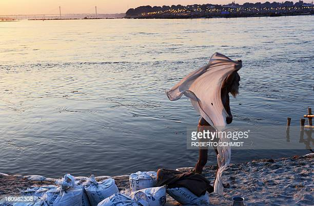 An Indian devotee wraps himself in a dhoti after taking a 'holy dip' in the waters of Sangam or confluence of the Yamuna Ganges and mythical Sarawati...