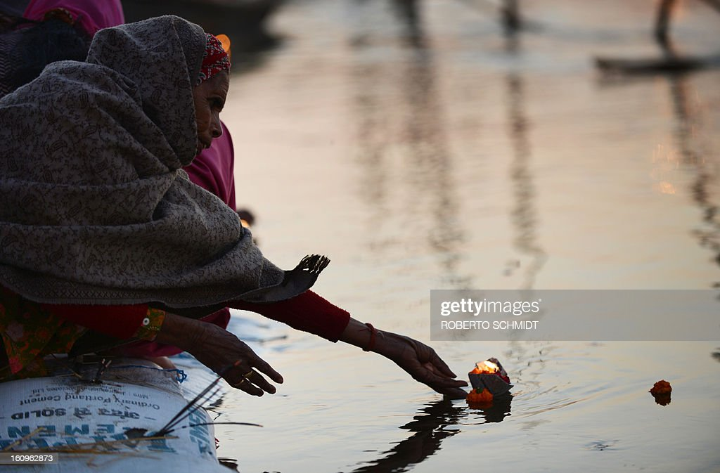 An Indian devotees releases an offering in the waters of Sangam or confluence of the Yamuna, Ganges and mythical Sarawati rivers at sunset during the Maha Kumbh festival in Allahabad on February 8, 2013. The Kumbh Mela in the town of Allahabad will see up to 100 million worshippers gather over 55 days to take a ritual bath in the holy waters, believed to cleanse sins and bestow blessings.