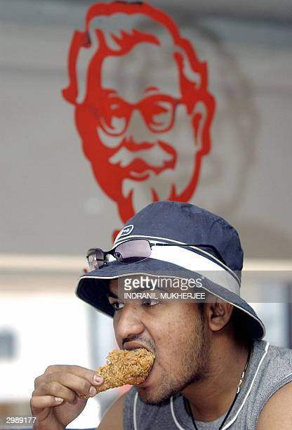 An Indian diner bites on a crispy fried chicken legpiece at a Kentucky Fried Chicken outlet in Bangalore 17 February 2004 Health officials from seven...
