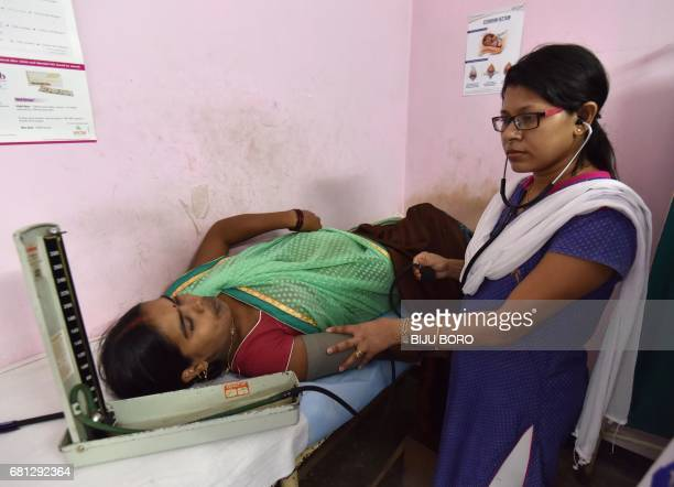 An Indian doctor examines an expectant mother during a free halth clinic for pregnant women at the Maternity and Child Welfare Hospital at Dhirenpara...