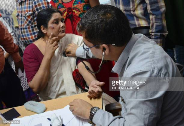 An Indian doctor examines Chandana Chakraborty after she was brought from a police station in Siliguri on February 22 for a medical check up to...
