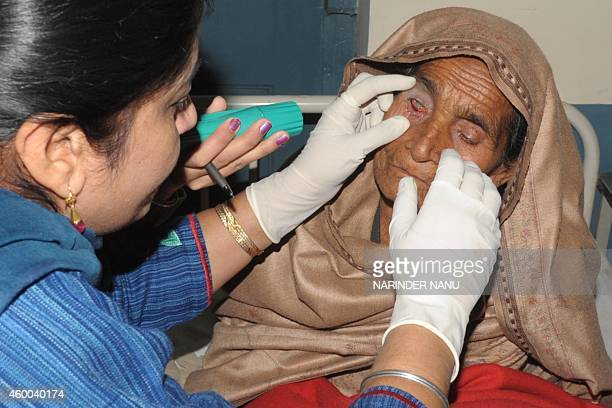 An Indian doctor inspects the eye of a patient who lost her eyesight after undergoing free cataract surgery at a government hospital in Amritsar on...