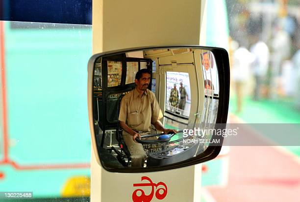 An Indian driver of The Andhra Pradesh State Road Transport Corporation is reflected in a mirror as he drives a newly equipped compressed natural gas...