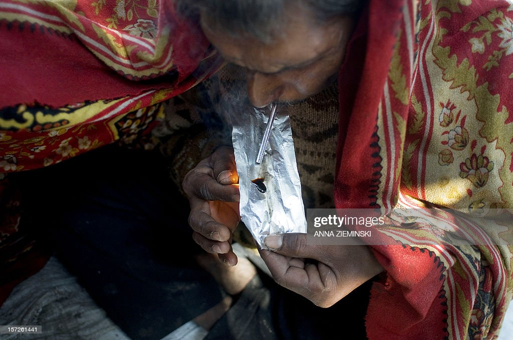 An Indian drug user covers himself with a blanket as he smokes smack,heroin, in the old sector of New Delhi on December 1, 2012. Drug use in India is on the rise but there are no proper statistics on the number of people suffering from this 'hidden disease' with the first and last national survey on drug abuse carried out in 2000-01 and showed a figure of 70 million drug users in the country. AFP PHOTO/ Anna ZIEMINSKI