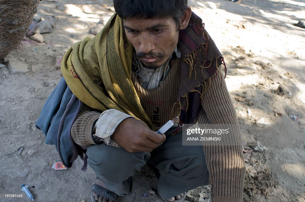 An Indian drug user holds a prepared syringe prior to injecting in the old sector of New Delhi on December 1, 2012. Drug use in India is on the rise but there are no proper statistics on the number of people suffering from this 'hidden disease' with the first and last national survey on drug abuse carried out in 2000-01 and showed a figure of 70 million drug users in the country. AFP PHOTO/ Anna ZIEMINSKI