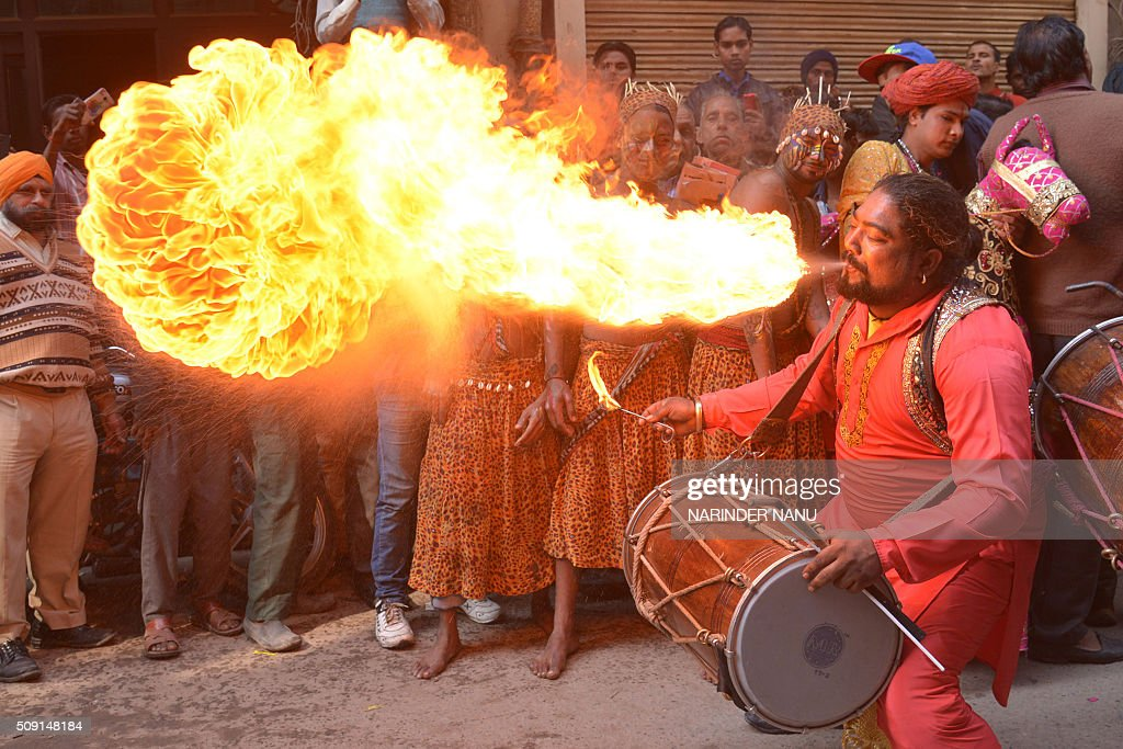An Indian drummer performs a fire breathing act during a procession to mark the 661st anniversary of the birth of Hindu guru Bawa Lal Dayal Maharaj in Amritsar on February 9, 2016. Bawa Lal Dayal Maharaj, a popular leader of his time, is especially revered by devotees of a temple in the town of Dhyanpur, some 45 kms north of Amritsar. AFP PHOTO/NARINDER NANU / AFP / NARINDER NANU
