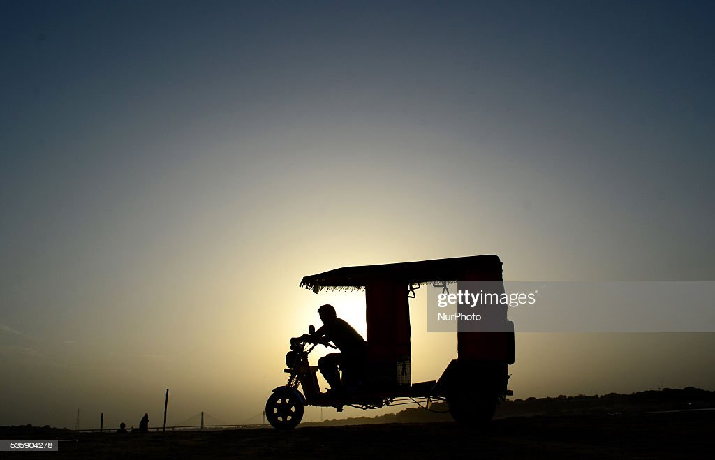 An indian electric rickshaw driver waits for passengers, on the banks of holy sangam,confluence of Ganges river,Yamuna river and mythical saraswati river,during sunset, in Allahabad on May 30,2016.