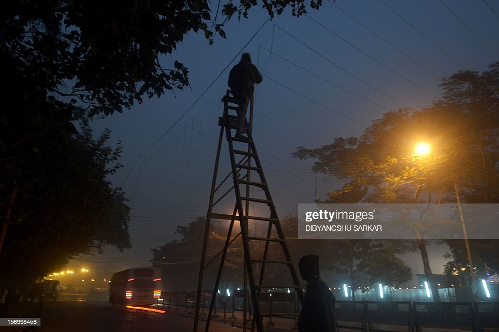 An Indian electrician adjusts decorative lights near the temporary camp for the Hindu Sadhus in Kolkata on January 5, 2013. Sadhus form all over the country started to gather in Kolkata on their way to the annual Hindu holy festival Gangasagar Mela, more that hundred thousand Hindu pilgrims will gather at the Gangasagar to take a dip in the ocean at the confluence of the River Ganges and the Bay of Bengal, on the occasion of Makar Sankranti, a holy day of the Hindu calendar considered to be of great religious significance in Hindu mythology. AFP PHOTO/ Dibyangshu SARKAR