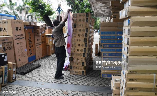 An Indian employee at an electronics store arranges items purchased before the implementation of the new Goods Services Tax for delivery in Kolkata...