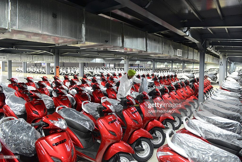 An Indian employee checks an Honda Activa scooter at the stock yard before delivery to different locations, at the second assembly line of Honda's fourth plant in India at Vithalapur, some 80 kms from Ahmedabad on June 29, 2016. The second assembly line was inaugurated June 29 by Keita Muramatsu, president and CEO of Honda Motorcycle and Scooter India (HMSI. Production expands by 0.6 million units to 1.2 million units annually at India's fourth plant at Vithalapur in Gujarat. / AFP / SAM