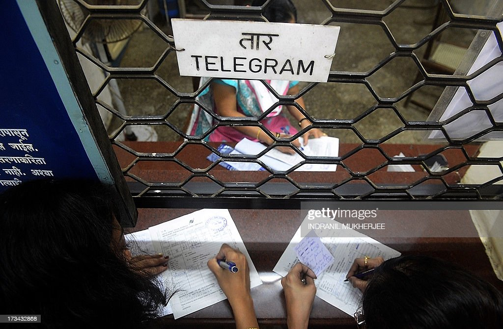 An Indian employee inspects a telegram as customers fill up more forms at a counter in Mumbai on July 14, 2013. Thousands of Indians crammed into telegram offices to send souvenir messages to friends and family in a last-minute rush before the service shuts down. July 14, 2013, is the last day that messages will be accepted by the 162-year-old service, the last major commercial telegram operation. In the days before mobile phones and the Internet, the telegram network was the main form of long-distance communication, with 20 million messages dispatched from India during the subcontinent's bloody partition in 1947. AFP PHOTO / INDRANIL MUKHERJEE