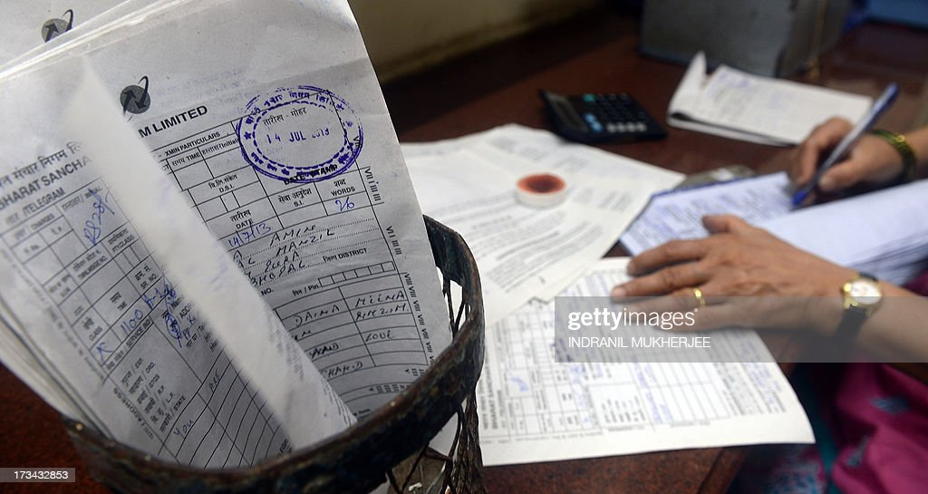 An Indian employee inspects a telegram form in Mumbai on July 14, 2013. Thousands of Indians crammed into telegram offices to send souvenir messages to friends and family in a last-minute rush before the service shuts down. July 14, 2013, is the last day that messages will be accepted by the 162-year-old service, the last major commercial telegram operation. In the days before mobile phones and the Internet, the telegram network was the main form of long-distance communication, with 20 million messages dispatched from India during the subcontinent's bloody partition in 1947. AFP PHOTO / INDRANIL MUKHERJEE