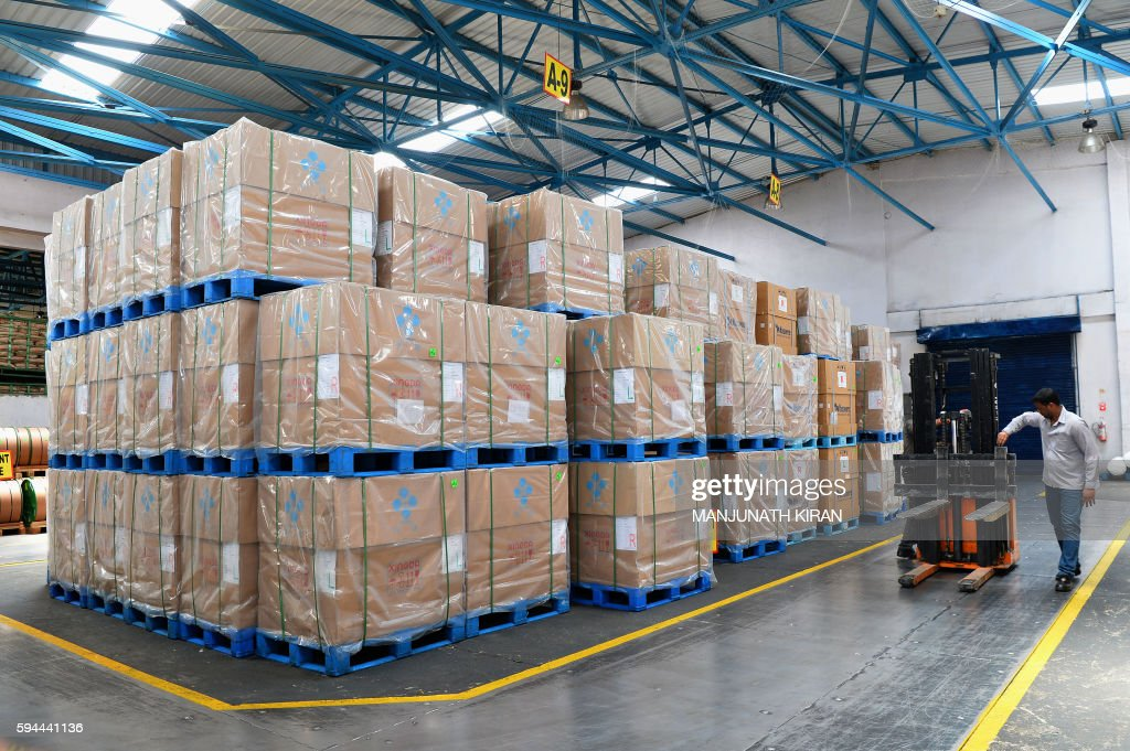 An Indian employee moves raw material through a storage area at the JK Tyre and Industries Limited manufacturing plant in Mysore on August 23 2016 /...
