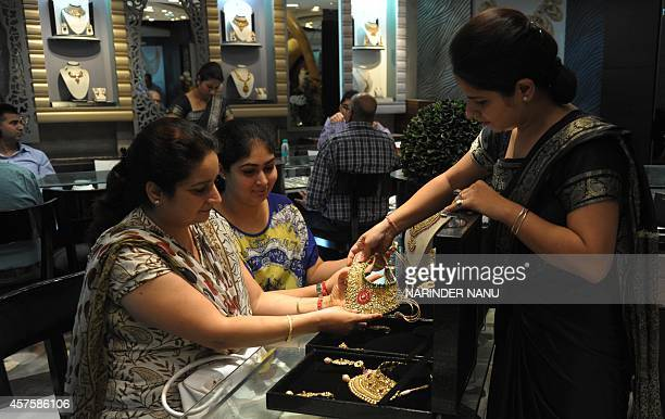 An Indian employee shows gold jewellery to a prospective customer at a jewellery store on Dhanteras in Amritsar on October 21 2014 Dhanteras which...