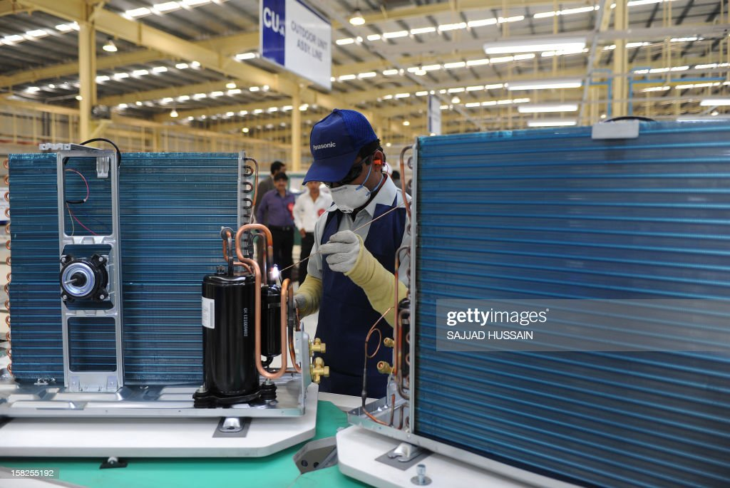 An Indian employee works on an air conditioning unit at the Panasonic 'eco ideas' factory at Jhajjar in Haryana on December 12, 2012. Panasonic India today announced the expansion of its presence in India with the opening of its first model 'eco ideas' factory. This is the company's latest initiative to showcase best practices in sustainable manufacturing and raise level of eco consciouness in the community through outreach activities. AFP PHOTO/SAJJAD HUSSAIN