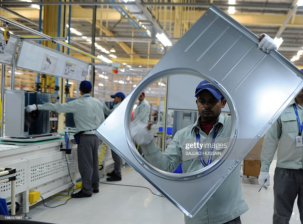 An Indian employee works on an air conditioning unit at the Panasonic 'eco ideas' factory at Jhajjar in Haryana on December 12, 2012. Panasonic India today announced the expansion of its presence in India with the opening of its first model 'eco ideas' factory. This is the company's latest initiative to showcase best practices in sustainable manufacturing and raise level of eco consciouness in the community through outreach activities.