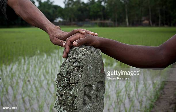 An Indian enclave resident and Bangladeshi citizen hold the border post that separates the enclave from the rest of Bangladesh July 10 2015 in...