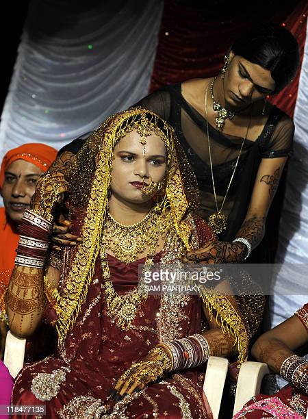 An Indian eunuch has wedding attire adjusted by another during their wedding reception in Ahmedabad on July 12 2009 In the presence of some one...