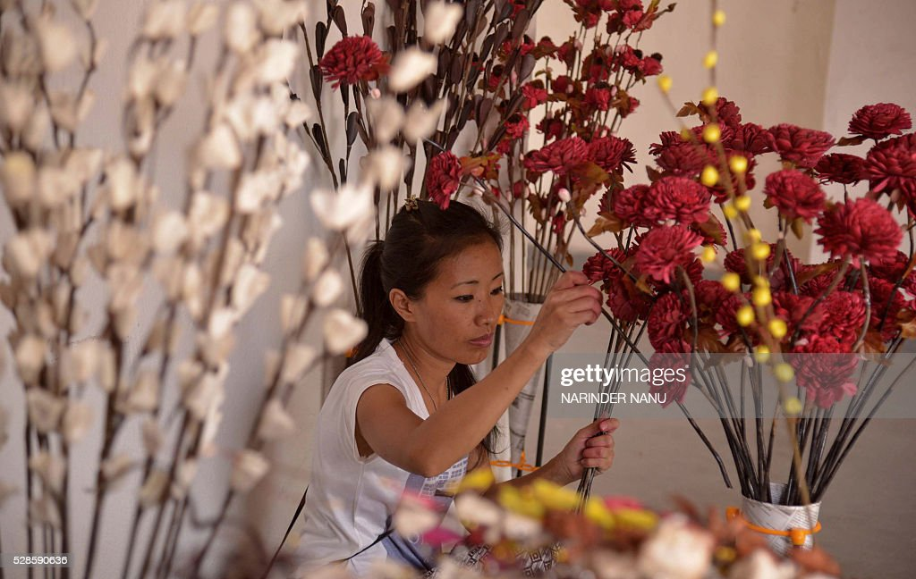 An Indian exhibitor arranges handmade flowers for display during the inauguration ceremony of the 'Amritsar Heritage Fair' in Amritsar on May 6, 2016. Hundreds of exhibitors from across the country are visiting the city to display their products during the fair which runs from May 6-20, in the northern Indian city. / AFP / NARINDER