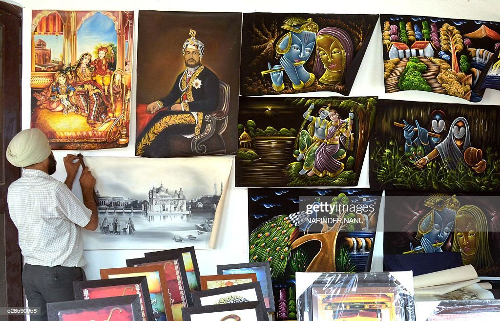 An Indian exhibitor hangs paintings during the inauguration ceremony of the 'Amritsar Heritage Fair' in Amritsar on May 6, 2016. Hundreds of exhibitors from across the country are visiting the city to display their products during the fair which runs from May 6-20, in the northern Indian city. / AFP / NARINDER