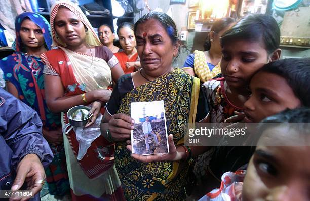 An Indian family member holds a picture of a victim of toxic homemade liquor consumption in Mumbai on June 19 2015 Fortyone people have died in...