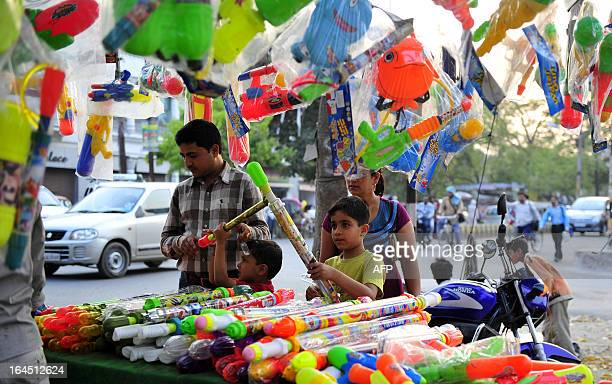 An Indian family purchase water guns from a roadside shop ahead of Holi festival in Allahabad on March 24 2013 Holi the popular Hindu spring festival...