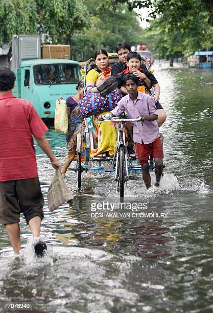 An Indian family ride a rickshaw to cross a waterlogged stretch of road at Bangur in Kolkata 28 September 2007 Twenty eight people died in the recent...