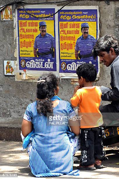 An Indian family sits on a pavement near posters of slain Liberation Tigers of Tamil Eelam leader Velupillai Prabhakaran in Mumbai on May 26 2009 Sri...