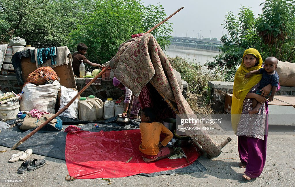 An Indian family takes shelter in a makeshift hut on higher ground after their homes were submerged in the rising waters of the Yamuna river in New Delhi on June 19, 2013. The monsoon, which India's farming sector depends on, covers the subcontinent from June to September, usually bringing some flooding. But the heavy rains arrived early this year, catching many by surprise and exposing the country's lack of preparedness. Military helicopters dropped emergency supplies to thousands of tourists and pilgrims stranded by flash floods that tore through towns and temples in northern India, killing at least 120 people, officials said. AFP PHOTO/ Prakash SINGH