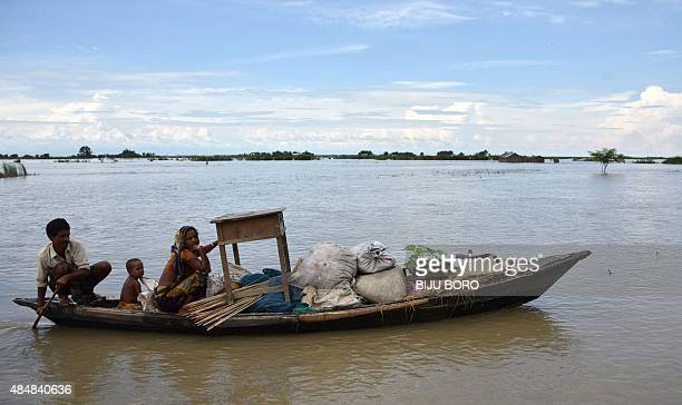 An Indian family travel with their belongings on a boat through flood water in Sandahkhati village some 80 km from Guwahati in Assam state on August...