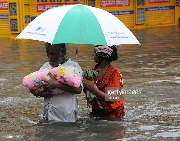 An Indian family wade through floodwaters in Chennai on December 2 2015 India has deployed troops to Tamil Nadu and closed the main airport there...