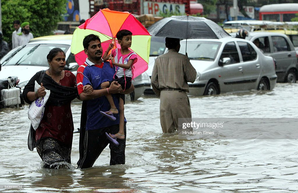 An Indian family walk through flooded streets after heavy rain showers at Naigaon on July 21, 2005 in Mumbai, India.